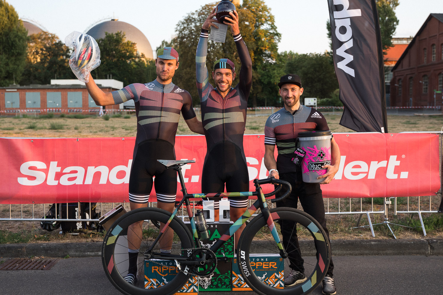 3 cyclists smiling to the camera while showing their trophies. An 8bar tmplhof is in front of them