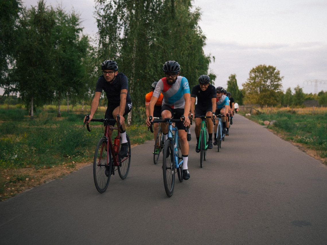 A group of cyclists riding on a rural road.They all ride two by two and wear complete cycling kits and helmets