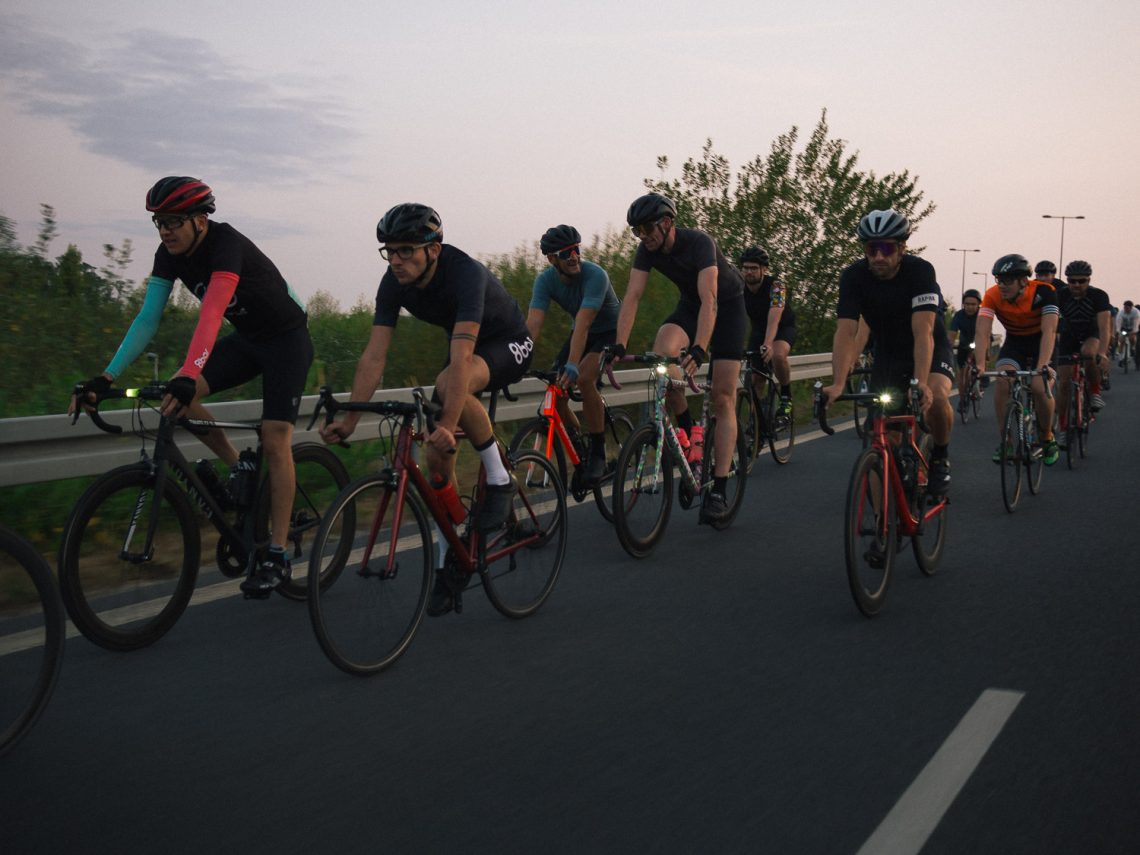Picture of a group of cyclists riding road bikes on an empty road in the sunset.