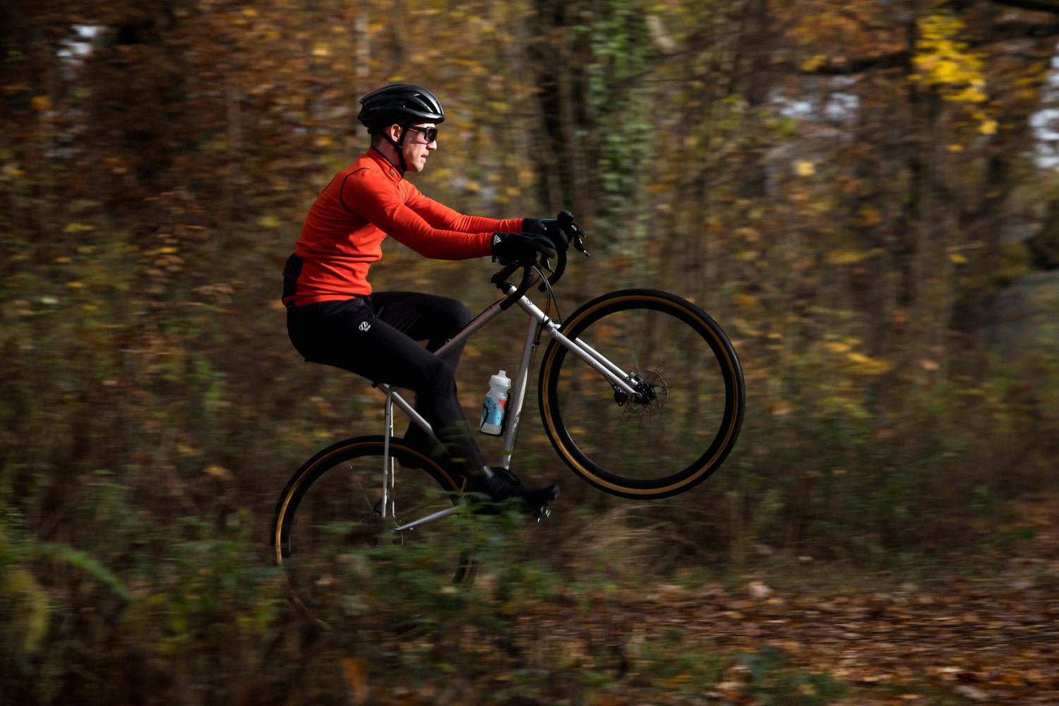 A man doing a wheeling on a gravel bicycle in the woods.He is riding a silver grey 8bar Mitte Steel.