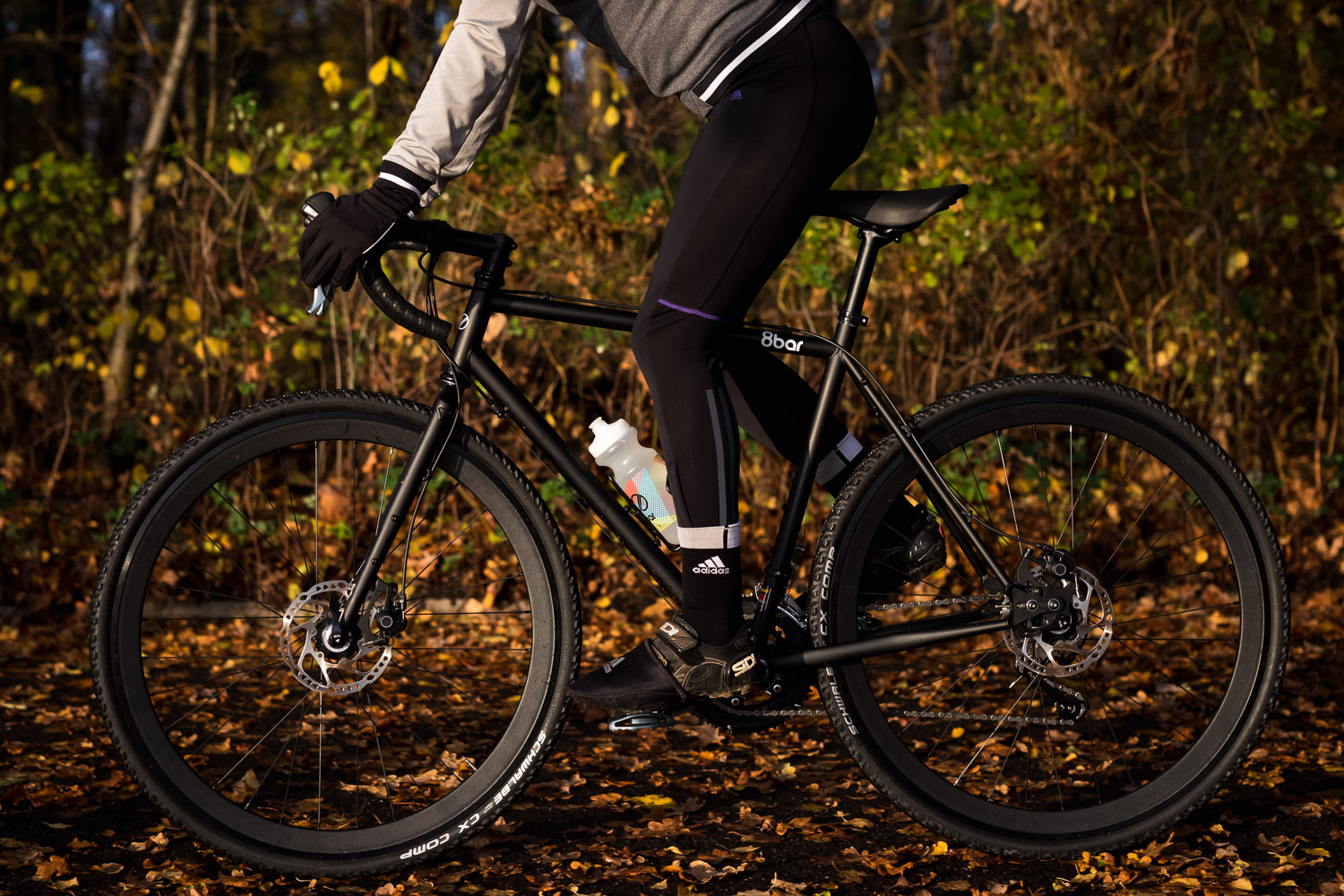 A woman riding a gravel bike in the woods.She is riding a black 8bar Mitte Steel.