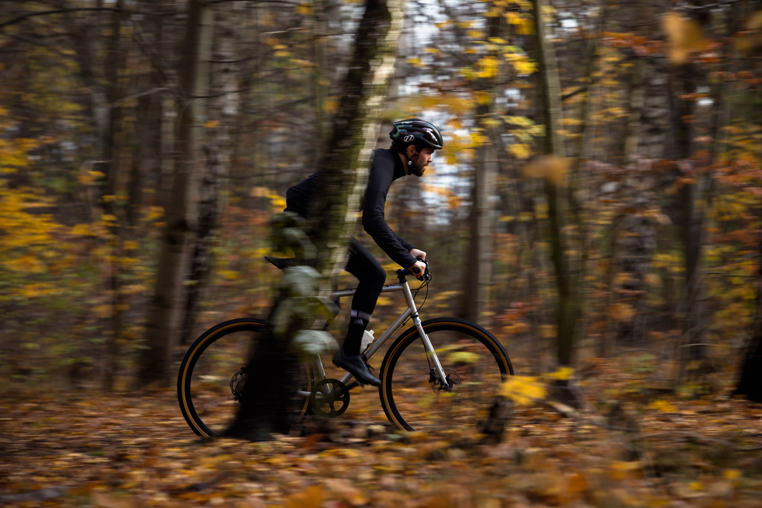 Picture of a man riding a gravel bike in the woods.He is riding a silver grey 8bar Mitte Steel
