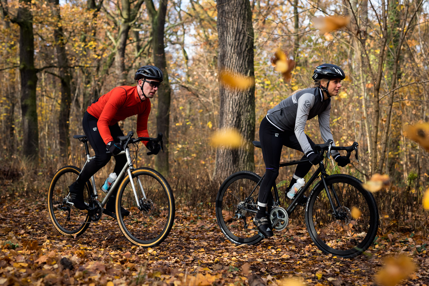 A man and a woman riding gravel bikes (8bar mitte steel) in the woods.