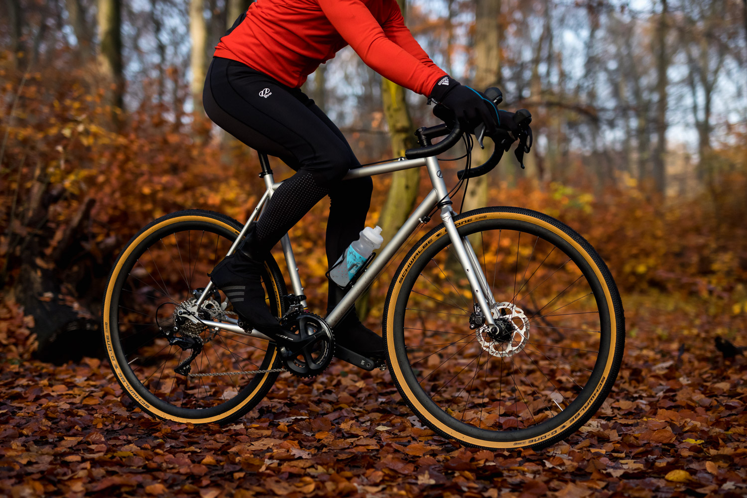 A man riding a gravel bike in the woods.He is riding a silver grey 8bar Mitte Steel.