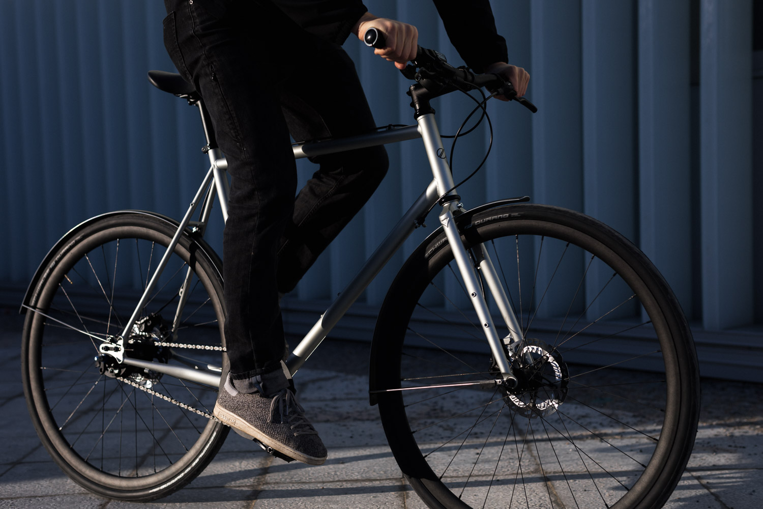 Bicycle ridden by a man wearing a full black outift.It is a silver grey 8bar Mitte Steel with fenders,riser bar and disc brakes.