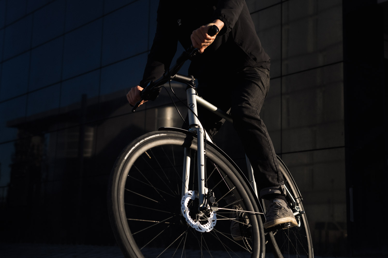 Bicycle ridden by a man wearing a full black outfit.It is a silver grey 8bar Mitte Steel with disc brakes, riser bar and fenders.