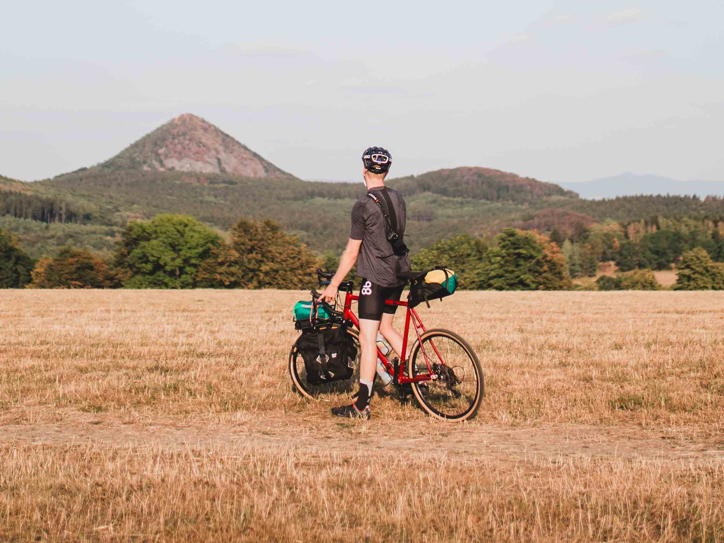 A cyclist is standing in the middle of a field on his bicycle while looking at the landscape, composed of hills and fields
