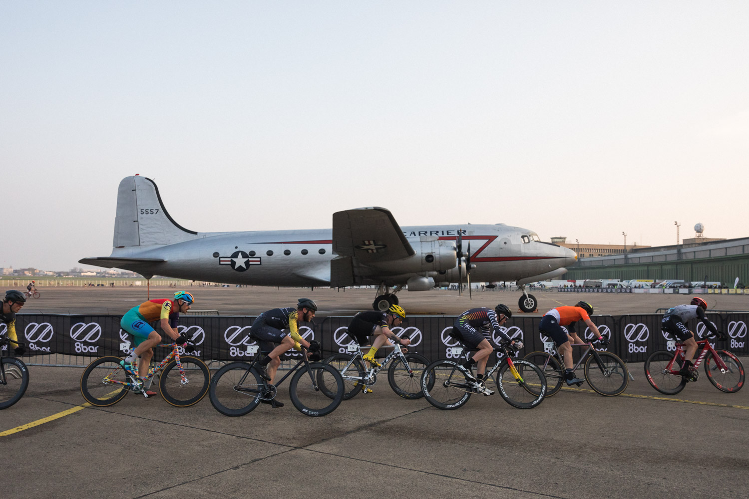 Picture of cyclists taking a long left turn during the 8bar crit 2018, a race for brakeless fixed gear bikes. The bikes in general are colorful, just as the cycling kits worn by the riders. The picture shows the bikes from the profile, riders go from the left of the picture to the right. In the background is a vintage silver airplane with a red line in form of Z painted on it. The clear sky occupies half of the picture.