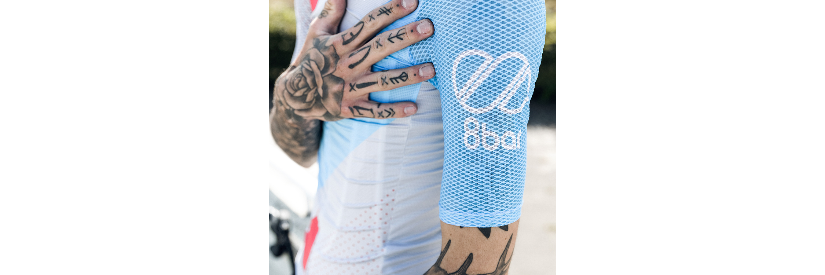 Picture of a tattooed man's trunk wearing a cycling jersey, the 8bar club jersey. His right hand is on his left pectoral.